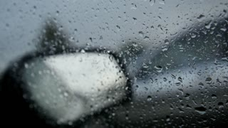 Car glass on a rainy day - defocused background. Moving waterdrops in the wipers of the windshield