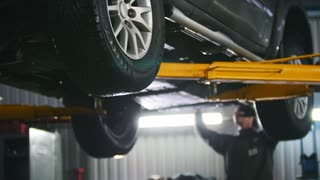 Car lifted in automobile service for repairing, worker fixing faults