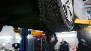 Car lifted in automobile service for repairing, workers fixing faults, slider