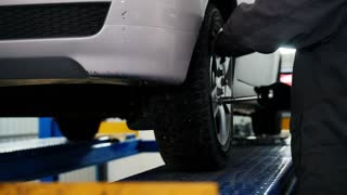 Car mechanic screwing pin car wheel of automobile in garage, slider
