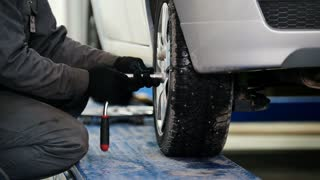 Car mechanic screwing pin car wheel of automobile in service