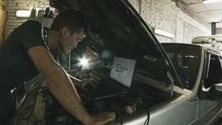 Car service, computer diagnostics: mechanic repairs the damage using the pc in car service, slider