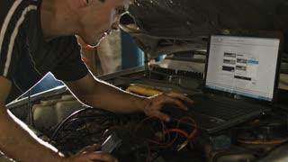 Car service, computer diagnostics: mechanic repairs the damage using the pc under the hood in car service, slider move