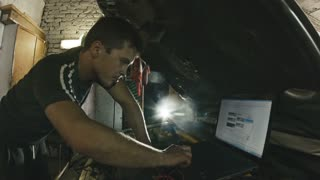 Car service, computer diagnostics: mechanic repairs the damage using the pc