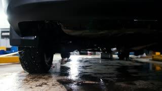 Car service - the bottom of the car on oiled floor
