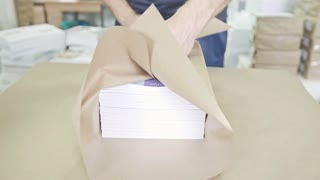 Close up man's hands packing boxes of sellotape in printing industry, front view