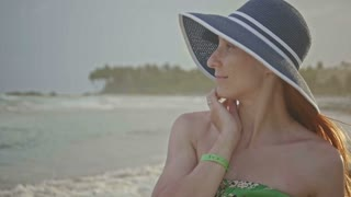 Close up portrait of beautiful young woman with freckles in hat posing on tropical beach slow motion, Dominican Republic