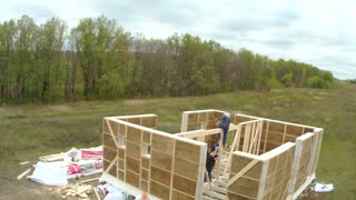 Country house of straw bales construction. Workers make interior walls in the country house, time-lapse