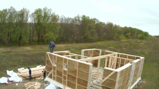 Country house of straw bales construction. Workers make second floor in house, time-lapse