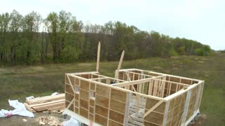 Country house of straw bales construction. Workers making window on second floor in house, time-lapse