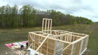 Country house of straw bales construction. Workers making windows on second floor in house, time-lapse