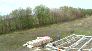 Country house of straw bales construction. workers set floor beams, time-lapse