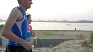 Couple of young adult athletes: woman and man running along promenade of river. Healthy lifestyle concept, slow-motion