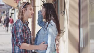 Cute girl and boy with long hair kissing on the street
