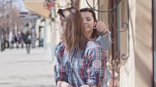 Cute girl and boy with long hair posing on street
