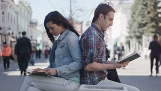 Cute girl and boy with long hair reads books on a street time-lapse