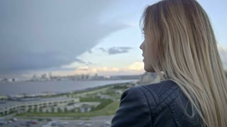 cute girl with long blonde hair in leather jacket straightens hair looking to the modern city slo-mo