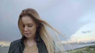 cute girl with long blonde hair with blue yeys in leather jacket straightens hair looking to the sky slo-mo