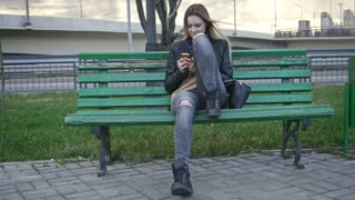Cute happy girl with long blonde hair in leather jacket straightens hair use gadget sitting on the bench 4k