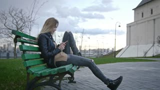 Cute happy girl with long blonde hair in leather jacket straightens hair use gadget sitting on the bench