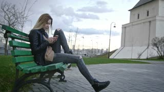 cute happy girl with long blonde hair in leather jacket straightens hair use phone sitting on the bench
