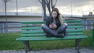 Cute happy girl with long blonde hair in leather jacket straightens hair with runny nose use gadget sitting on the bench in the wind 4k