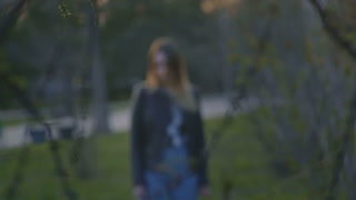 Cute young girl standing in the park at dusk