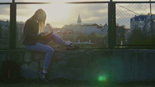 Cute young girl uses gadget seated on the playground at sunset