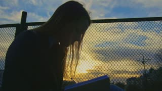 Cute young girl writing diary seated on the playground at dusk silhouette