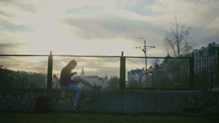 Cute young girl writing diary seated on the playground at dusk wide angle