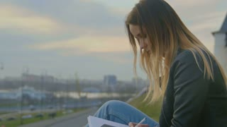 Cute young girl writing diary sits on a background of city views at dusk close up
