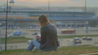 Cute young girl writing diary sits on a background of city views at dusk narrow