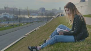 Cute young girl writing diary sits on a background of city views at dusk