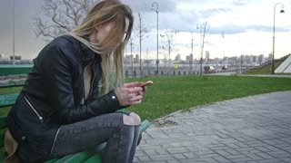 dissapointed girl with long blonde hair in leather jacket straightens hair use gadget sitting on the bench in the wind 4k