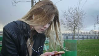 Dissapointed girl with long blonde hair in leather jacket straightens hair use gadget sitting on the bench in the wind listen headphones 4k close-up