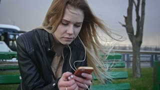 Dissapointed girl with long blonde hair in leather jacket straightens hair use gadget sitting on the bench in the wind listen headphones close-up, slo-mo