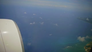 Dominican Republic aerial view from the plane window. Under the wing of the aircraft visible coast of caribbean sea
