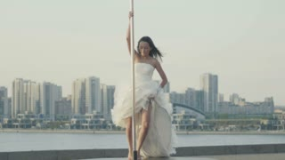 Fit attractive girl dancing on the portable pole at summer day in wedding dress over the skyline, slow-motion, telephoto