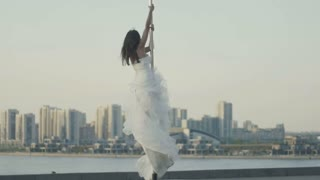 Fit attractive girl posing on the portable pole at summer day in wedding dress over the skyline, slow-motion, telephoto