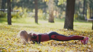 Fitness woman strength training doing workout at sunny autumn park. Fit caucasian sporty girl exercising her body - does push-UPS on yellow leaves