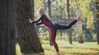Fitness woman strength training doing workout at sunny autumn park. Fit caucasian sporty girl exercising her body near tree - lifts legs alternately