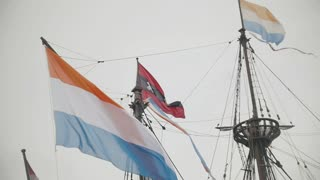 Flag of Netherlands and the symbol of Amsterdam - triple x flying on building in Amsterdam, Holland, slow-motion, slow-motion