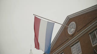 Flag of Netherlands flying on building in Amsterdam, Holland, slow-motion