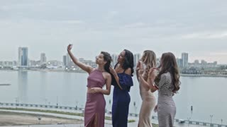 Four Attractive young women in party dresses on high hill get a selfie, wide shot