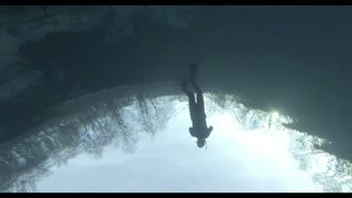 Free diver swimming underwater in blue lake