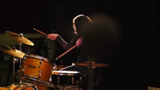 Girl drummer, attractive young woman plays the drums
