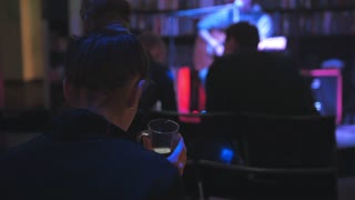 Girl in night club drink coffee during rock guitarist at scene plays guitar for spectators