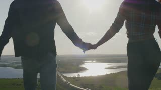 Group Of Friends Hold Hands on a high hill at sunset And Run Away From Camera ,Slow Motion