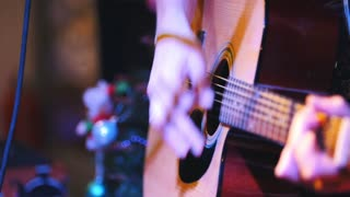Guitarist holds acoustic guitar near microphone at concert in club, extremely close up