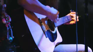Guitarist is holding acoustic guitar near microphone at concert in club